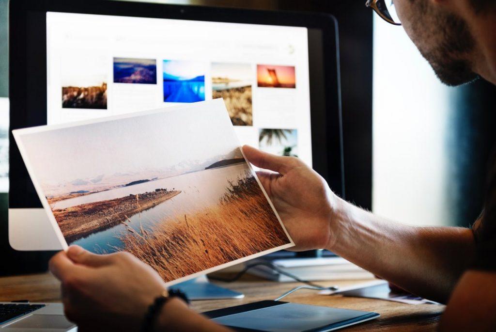 אדם מביט על תמונה שהדפיס במדפסת תמונות מקצועית